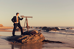 A young businessman in suit stands on a California beach forecasting a good business future. His telescope sits on a rock while the surf rolls in.